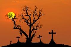 L'arbre mort de silhouette effrayante et la silhouette fantasmagorique croise dans le cimetière mystique avec la demi-lune Photos stock