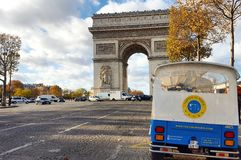 L& x27;Arc de​ Triomphe and the thai tuk tuk, champs elysees, Paris, France. View of the landmark of napoleon from avenue des champs elysees, in the period Royalty Free Stock Photo