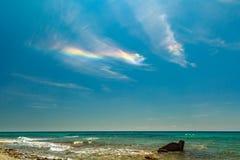 L'arc-en-ciel à la côte rocheuse donnant sur le bleu de turquoise Image stock