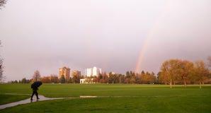 L'arc-en-ciel apparaît au-dessus du parc pendant le parapluie de piéton d'orage Photographie stock libre de droits