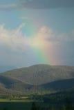 L'arc-en-ciel au-dessus de l'arbre a couvert des collines Photos libres de droits