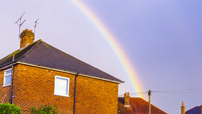 L'arc-en-ciel fin au-dessus du toit rouge a brillé avec le soleil Photographie stock libre de droits