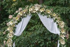 L'arcade de mariage avec des fleurs a arrangé en parc pour une cérémonie de mariage Photo stock