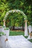 L'arcade de mariage avec des fleurs a arrangé en parc pour une cérémonie de mariage Photographie stock