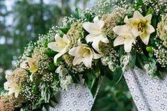 L'arcade de mariage avec des fleurs a arrangé en parc pour une cérémonie de mariage Images stock