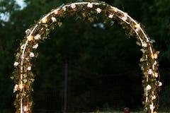 L'arcade florale fraîche élégante de bas-côté de mariage avec des feuilles fleurit a Photo stock