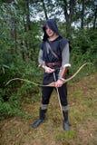 L'archer médiéval avec le capot noir et les flèches colorées dans le tremblement se tient avec la flèche Photographie stock libre de droits