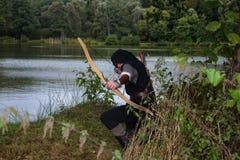 L'archer médiéval avec le capot noir se met à genoux au sol avant un lac, vise avec la flèche et la courbe en avant Images stock