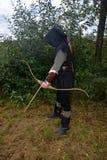 L'archer médiéval du côté se tient avec le capot noir et avec l'arc tendu et avec la flèche Images stock