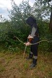 L'archer médiéval du côté se tient avec le capot noir et avec l'arc tendu et avec la flèche Photos stock