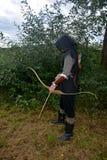 L'archer médiéval du côté se tient avec le capot noir et avec l'arc tendu et avec la flèche Image libre de droits