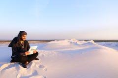L'architecte masculin arabe bel regarde des documents et s'assied sur SA photo libre de droits