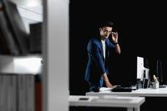 L'architecte professionnel élégant en verres habillés dans une veste à carreaux bleue se tient à côté du bureau avec l'ordinateur images stock