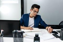 L'architecte s'est habillé dans une veste bleu-foncé travaille avec des documents sur le bureau dans le bureau photographie stock