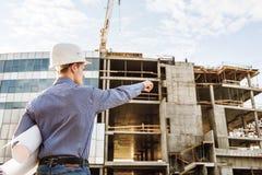 L'architetto con i disegni indica sulla facciata della costruzione immagine stock libera da diritti