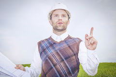L'architetto dell'ingegnere in casco ed in disegni bianchi ritiene, analizza, fornisce la buona idea o soluzione al problema comp Fotografia Stock Libera da Diritti