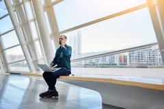 L'architetto dell'uomo che parla sul telefono delle cellule durante crea un progetto di costruzione sul computer portatile Fotografia Stock Libera da Diritti