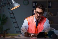 L'architetto della costruzione che lavora tardi ai disegni alla notte Fotografia Stock