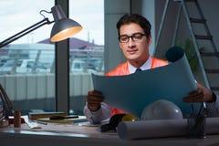 L'architetto della costruzione che lavora tardi ai disegni alla notte Fotografie Stock