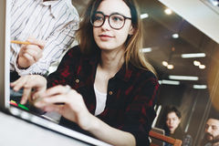 L'architetto della giovane donna mostra un nuovo progetto su un computer portatile moderno Partenza in sottotetto moderno Fotografia Stock