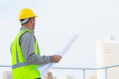 L'architetto nella tenuta protettiva degli abiti da lavoro blueprints all'aperto Immagine Stock