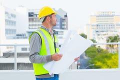 L'architetto nella tenuta protettiva degli abiti da lavoro blueprints all'aperto Immagine Stock Libera da Diritti