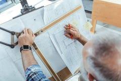 L'architetto senior con esperienza sta lavorando al suo progetto immagine stock libera da diritti