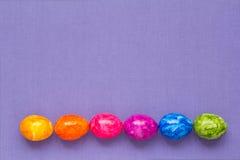 L'arcobaleno delle uova di Pasqua colora il lillà Fotografie Stock Libere da Diritti
