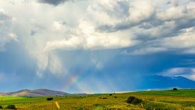 L'arcobaleno emette luce alla luce solare contro lo sfondo delle nuvole scure Le ombre del sole si muovono lungo i giacimenti di  archivi video