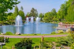 L'area del parco con un lago e gli ambiti di provenienza su contro lo sfondo degli alberi verdi e delle piante ornamentali Immagine Stock