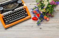 L'area di lavoro con la macchina da scrivere d'annata arancio con un mazzo del campo dell'estate fiorisce Immagine Stock Libera da Diritti