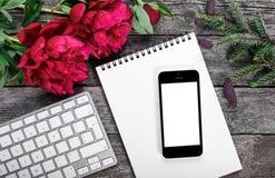 L'area di lavoro con lo smartphone, la tastiera, il blocco note, il ramo dell'abete e le peonie fiorisce il mazzo su fondo rustic Fotografia Stock