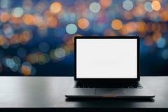 L'area di lavoro concettuale, computer portatile con lo schermo bianco in bianco sulla tavola, ha offuscato il fondo fotografie stock libere da diritti