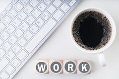 L'area di lavoro del computer con caffè ed i cubi con il ` di parola funzionano il ` Fotografie Stock Libere da Diritti