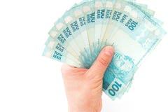 L'argent brésilien, reais, des dénominations élevées s'est tenu dans la paume de votre main Image stock