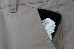 L'argent dans des poches de pantalon, dollars dans des jeans empoche Images stock