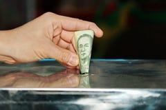 L'argent de baisses de bouddhistes a mis dans les boîtes de donation Photos stock