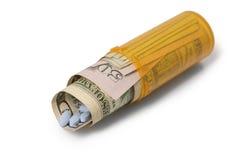 L'argent et les pilules ont roulé dans le récipient de prescription - pose du Dow photo libre de droits