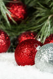 L'argent rouge ornemente la neige de pin Photos stock
