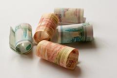 L'argent russe, billets de banque de cinq mille, mille et cinq cents roubles a roulé dans un tube photo stock