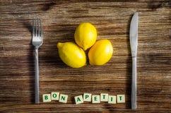 L'argenterie et les citrons sur la table en bois avec l'apetit de fève signent Photo stock