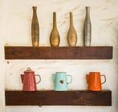 L'argilla al forno del vaso variopinto e la brocca dell'acciaio hanno messo sopra lo scaffale di legno Fotografia Stock