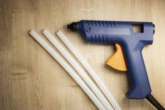 L'arme à feu de colle électrique avec du silicone colle sur une surface en bois images stock