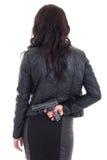 L'arme à feu de dissimulation de femme derrière elle a de retour isolé sur le blanc Photographie stock libre de droits