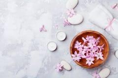 L'aromaterapia, stazione termale, fondo di bellezza con il ciottolo di massaggio, ha profumato i fiori innaffia e candele sulla v fotografie stock