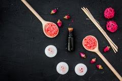 L'Aromatherapy pour détendent le concept Bourgeons de Rose, sel de station thermale, bougies et huile sur le copyspace noir de vu photos stock