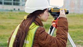 L'arpenteur de jeune femme dans les vêtements et le casque de travail verts ajuste l'équipement, produit des calculs et écrit au banque de vidéos
