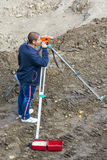 L'arpenteur fait des mesures avec l'aide d'un niveau workplace Photographie stock libre de droits