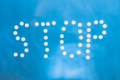 L'arrêt d'inscription présenté des pilules blanches sur un fond bleu photos libres de droits