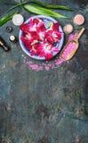 L'arrangement de station thermale avec des cuvettes de l'eau, des fleurs roses d'orchidée, le sel de mer, la crème cosmétique et  Photographie stock libre de droits